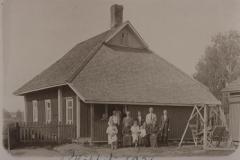 Puinen asuinrakennus ja ihmisiä ryhmäkuvassa